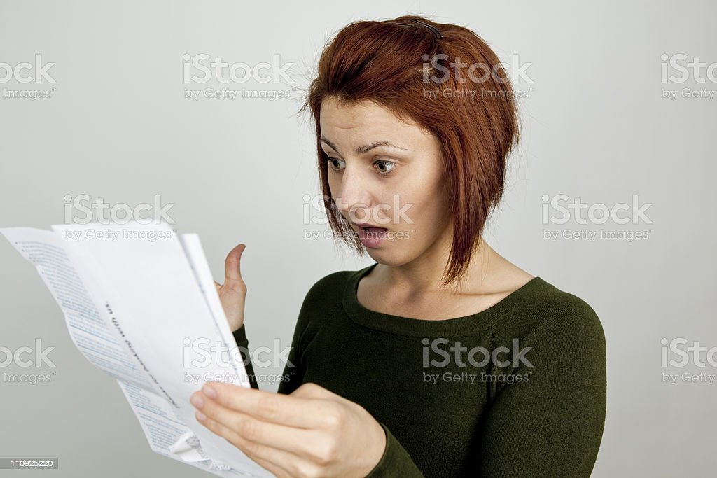 Shocked woman with wide open mouth receives credit card statement royalty-free stock photo