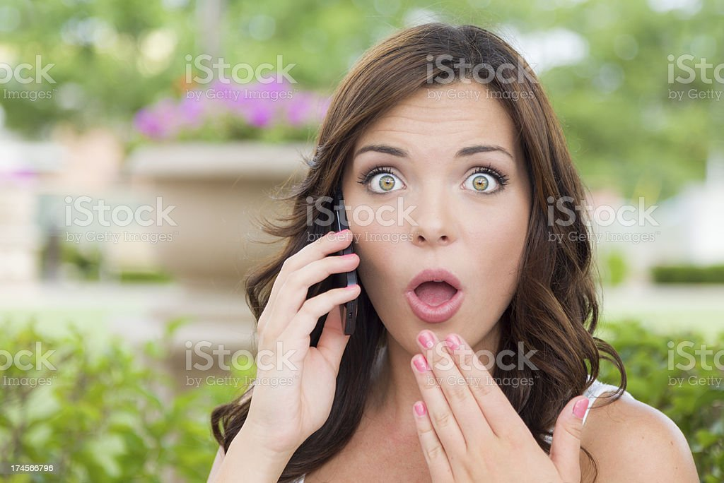 Shocked Young Adult Female Talking on Cell Phone Outdoors royalty-free stock photo