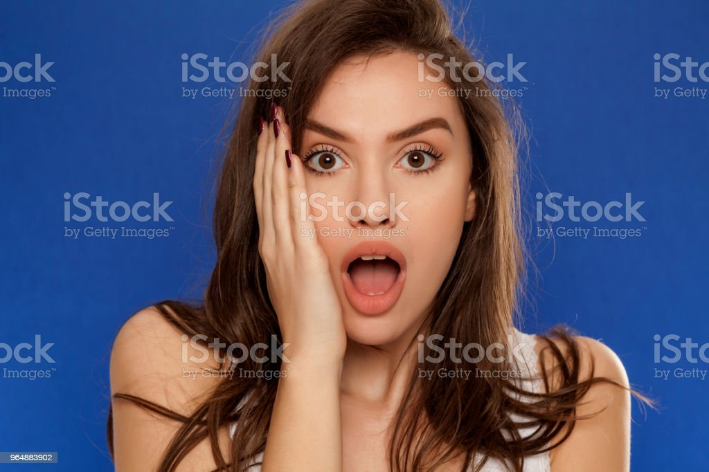 shocked young beautiful woman on blue background royalty-free stock photo
