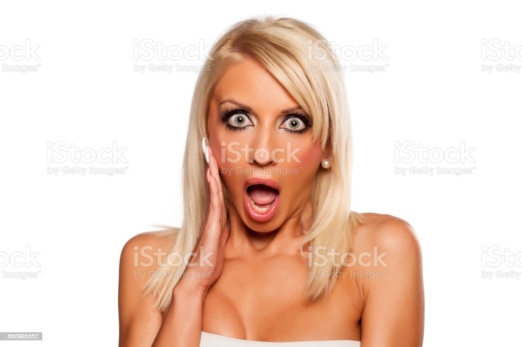 Shocked young blonde on a white background royalty-free stock photo