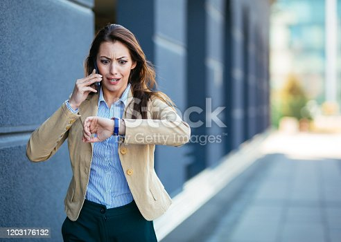 Shocked young businesswoman checking time on wristwatch while talking mobile phone
