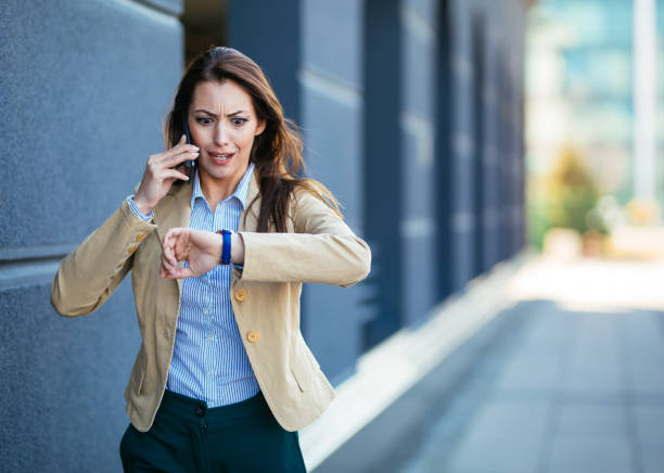 Shocked young businesswoman checking time on wristwatch while talking mobile phone stock photo