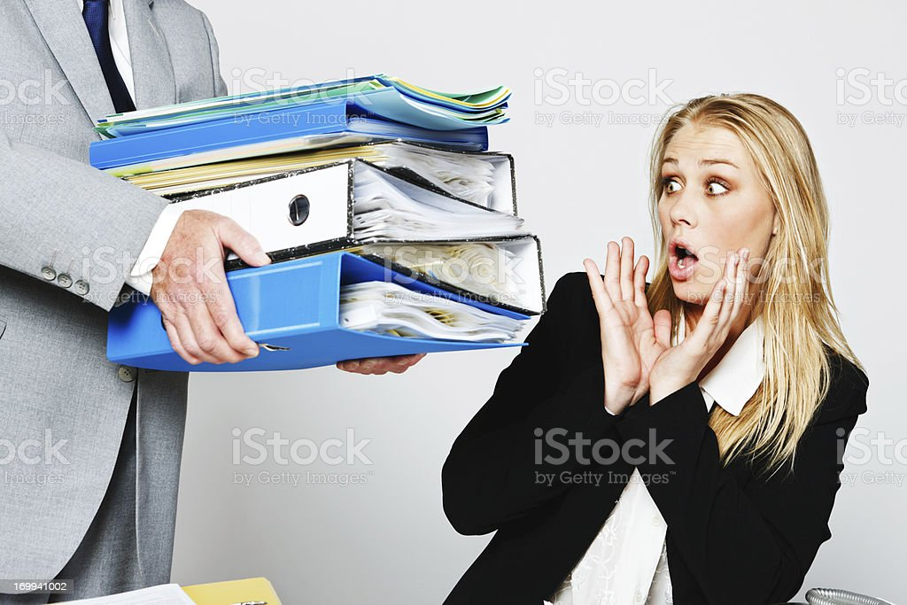 Shocked young businesswoman  gets handed huge workload royalty-free stock photo
