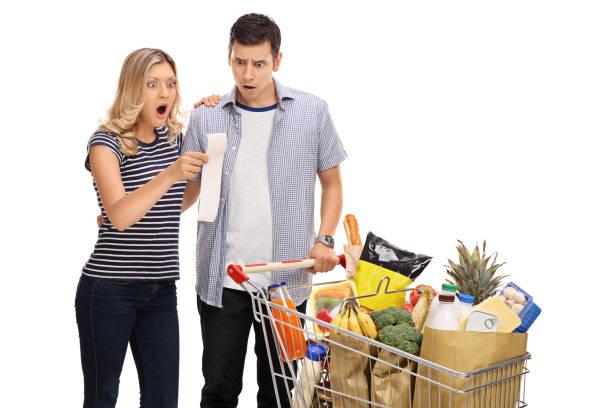 schockiert junges paar betrachten eine einkaufen rechnung - gefüllte bon bons stock-fotos und bilder