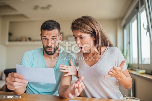 istock Shocked young couple looking at their bills at home 1018852324