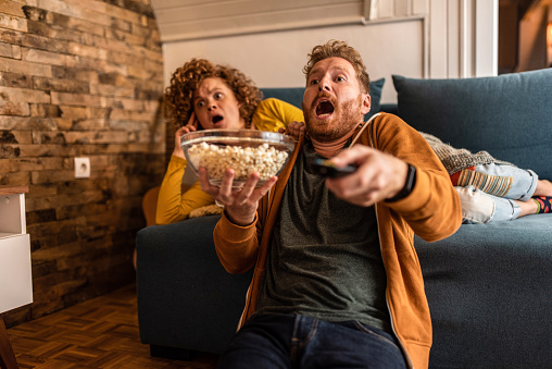 Shocked young ginger couple watching an event on tv.