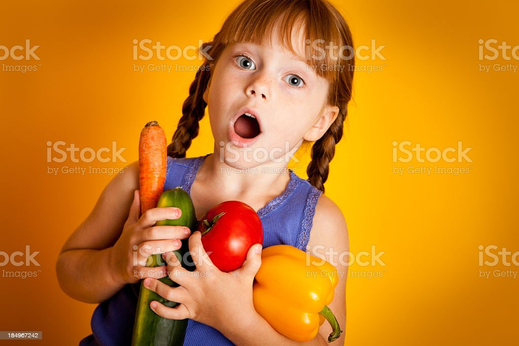 Shocked Young Girl Holding Carrot, Zucchini, Tomato, and Yellow Pepper royalty-free stock photo