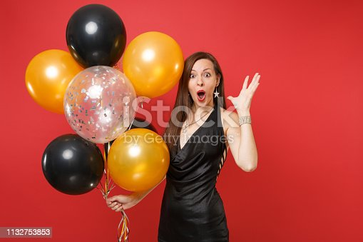 istock Shocked young girl in little black dress celebrating spreading hands, holding air balloons isolated on red background. International Women's Day, Happy New Year, birthday mockup holiday party concept. 1132753853