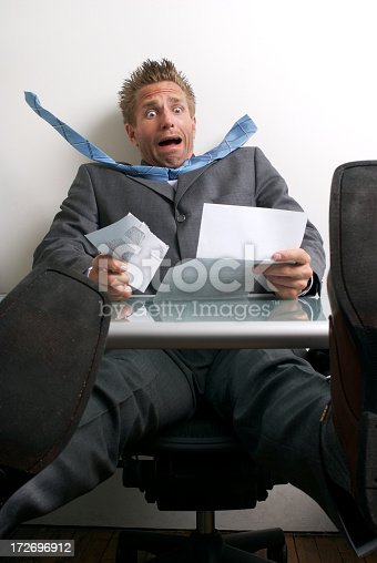 481644192 istock photo Shocked Young Man Businessman Sitting at Desk with Bill 172696912