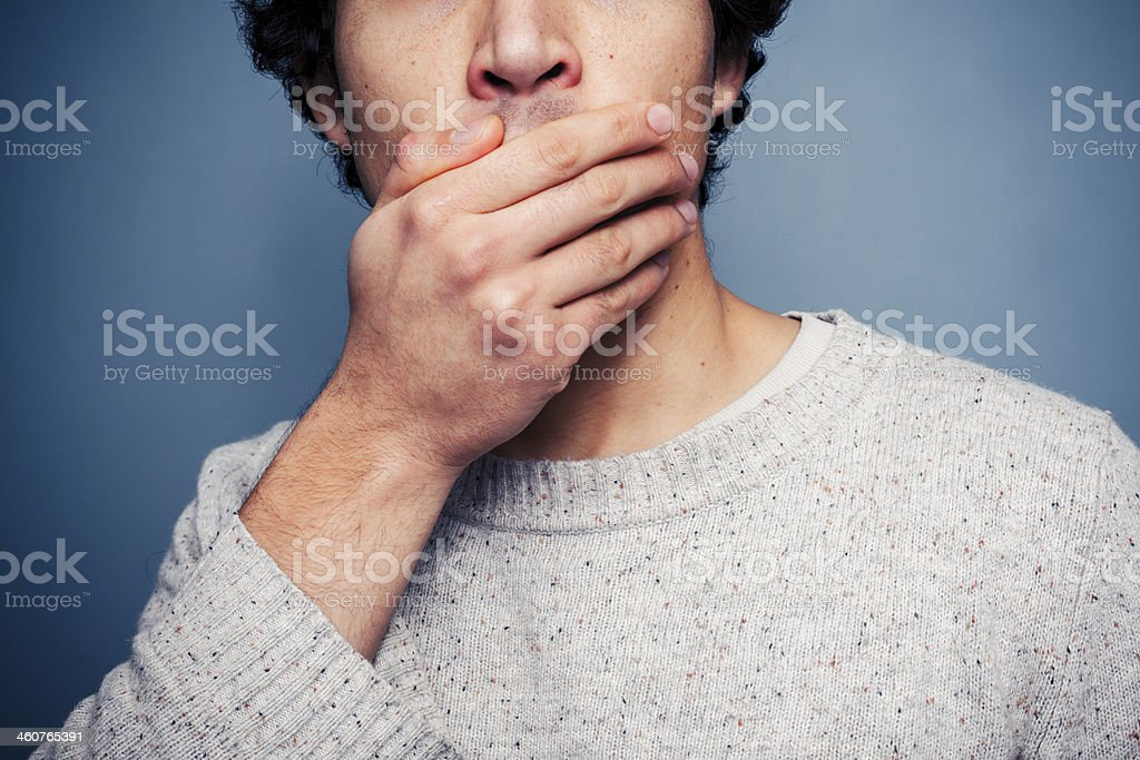 Shocked young man covering his mouth stock photo
