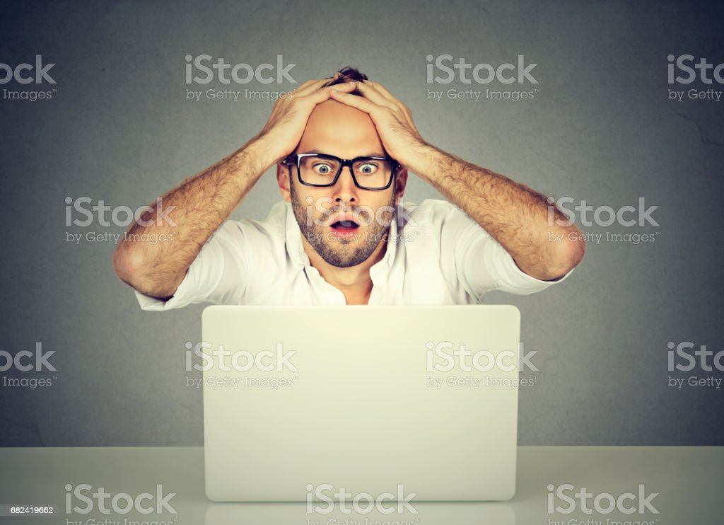 Shocked young man looking at laptop computer anxious with open mouth stock photo