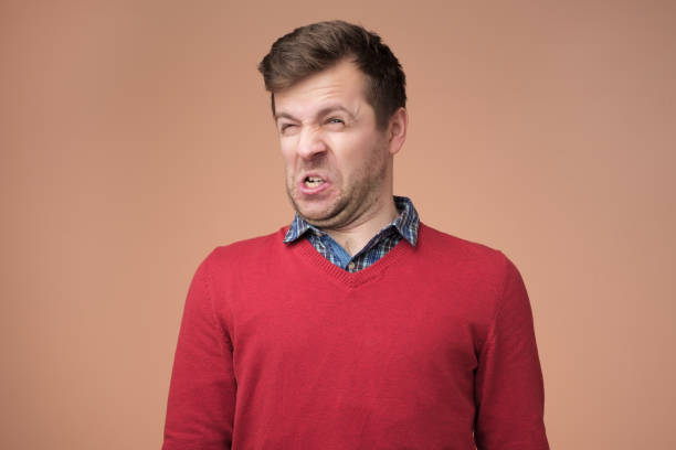 Shocked young man looking at something unpleasant and bad Disguting smell concept. Shocked young man looking at something unpleasant and bad, isolated on gray background. Negative emotion concept disgust stock pictures, royalty-free photos & images
