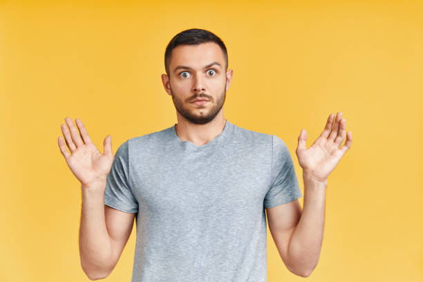 shocked young man with arms up looking amazed in camera over yellow background - omg stock photos and pictures