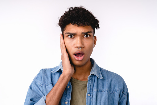 Shocked young mixed-race man in casual attire isolated over white