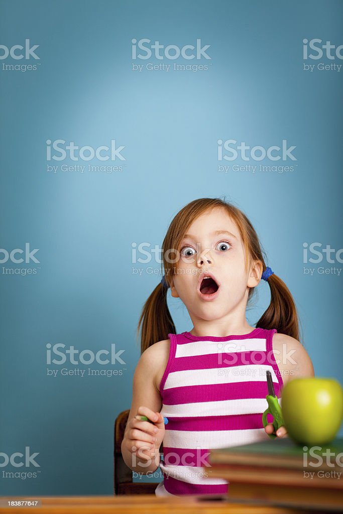Shocked Young Student Girl Sitting in School Desk stock photo
