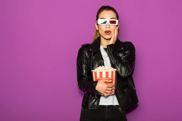 shocked young woman in 3d glasses eating popcorn and looking at camera isolated on violet stock photo
