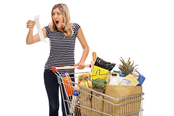 shocked young woman looking at a store receipt - gefüllte bon bons stock-fotos und bilder