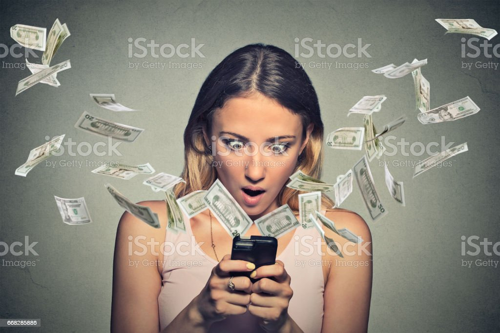 Shocked young woman using smartphone with dollar bills flying away from screen stock photo