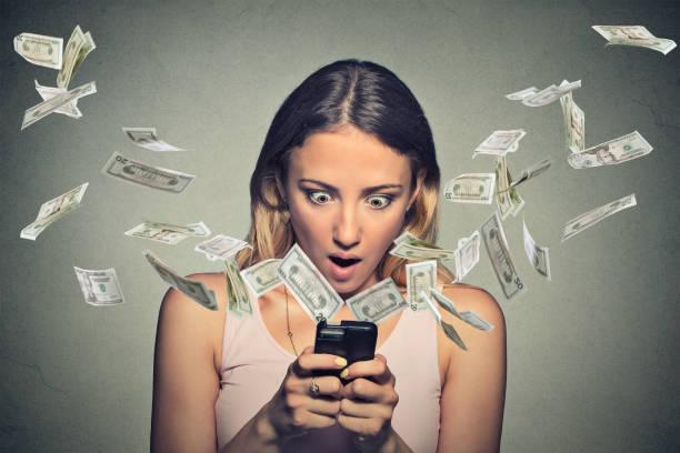 schockiert junge frau mit smartphone mit dollarnoten fliegen weg von bildschirm - free online game stock-fotos und bilder