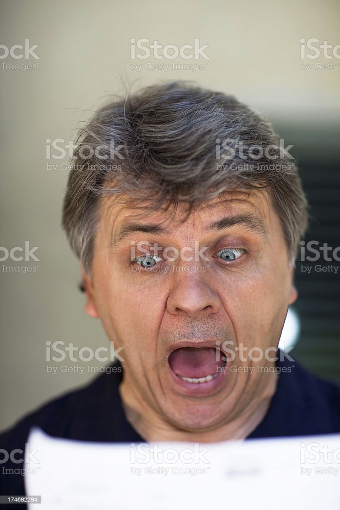Middle aged man looking at the paper with shocking expression.