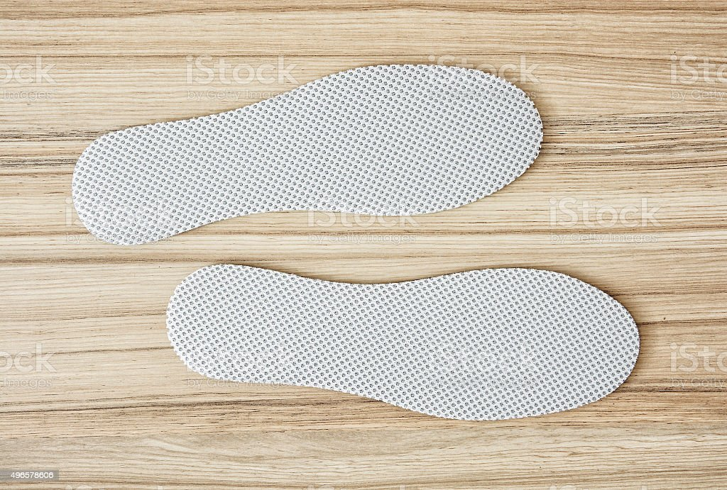 Shoe insoles on the wooden background stock photo