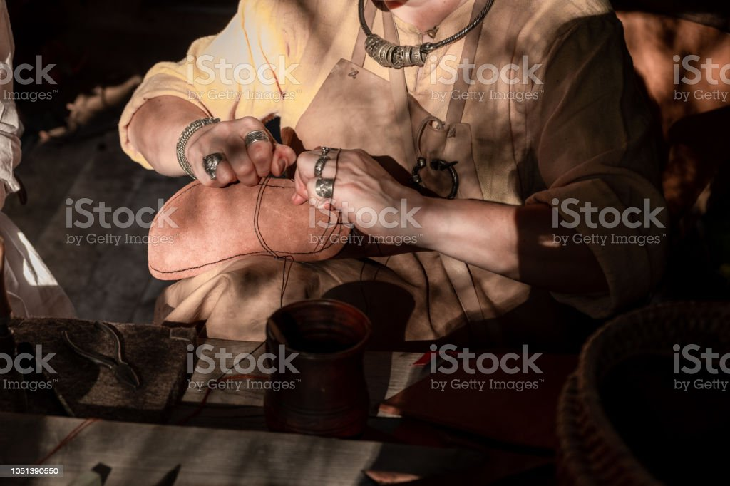 Shoe master sews shoes and leather. stock photo