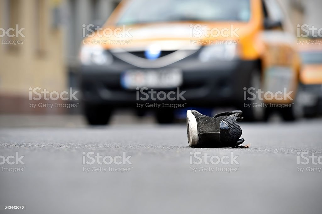 Shoe on the street with cars in background after accident stock photo