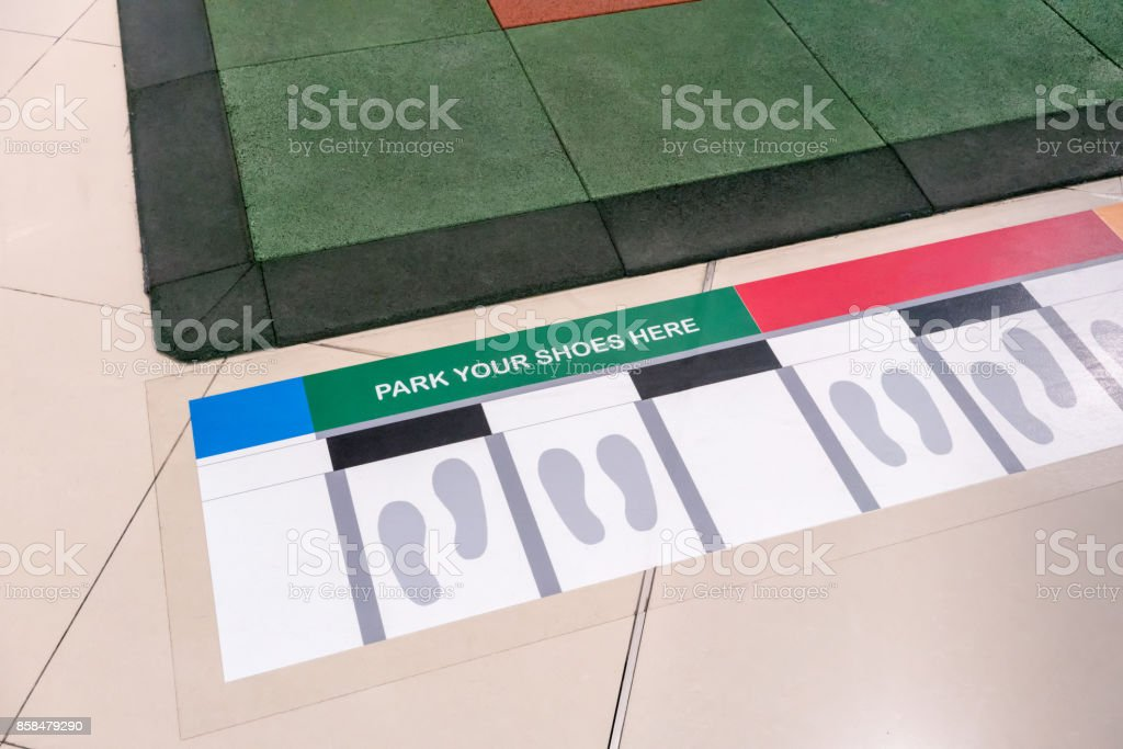 Shoe parking area. Painted white and grey footsteps between parallel grey lines on ceramic floor stock photo