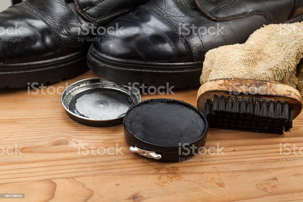 Shoe polish with brush, cloth and worn boots on platform stock photo