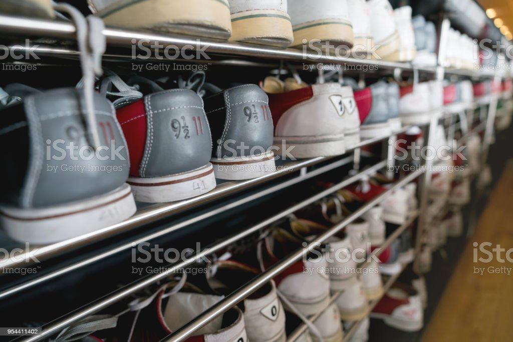 Shoe rack filled with bowling shoes stock photo
