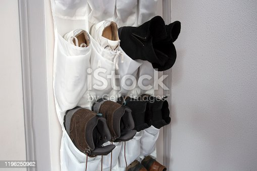 Shoe rack hanging on a wooden door, storage for shoes close-up