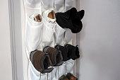 istock Shoe rack hanging on a wooden door, storage for shoes 1196250962