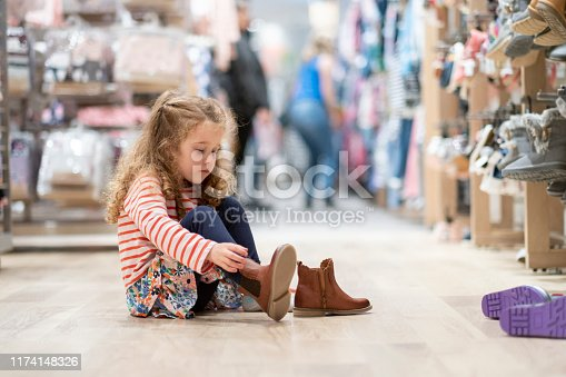 Little girl trying on shoes in a store.  Shoe shopping, shoes, children, store