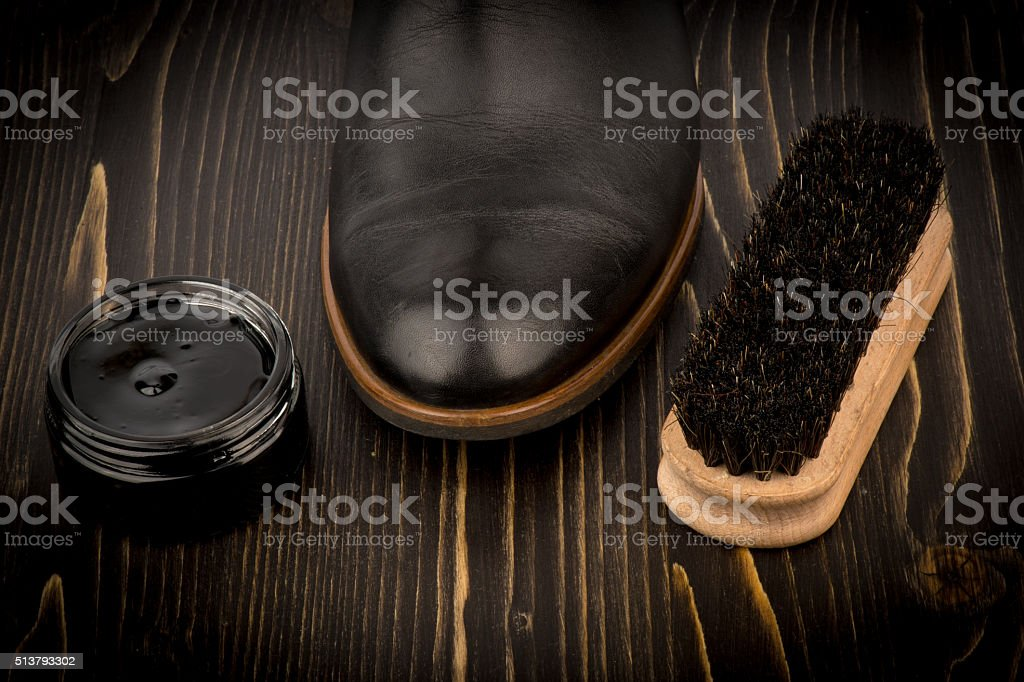 Shoe wax and brush on the wooden background. stock photo