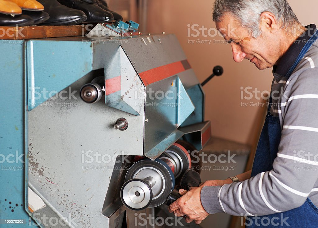 Shoemaker is polishing sole of shoe royalty-free stock photo