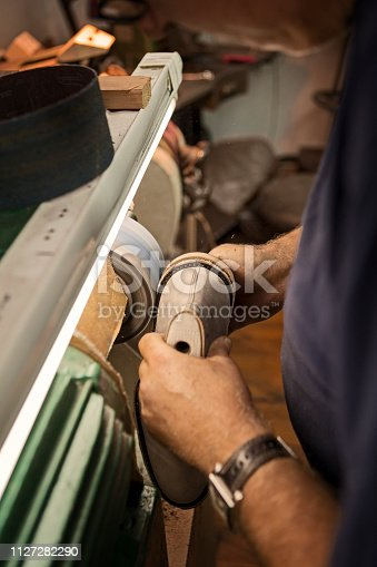 Polishing shoes in shoe maker workshop