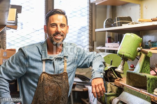 A Latino man is standing in a workshop and is making shoes.