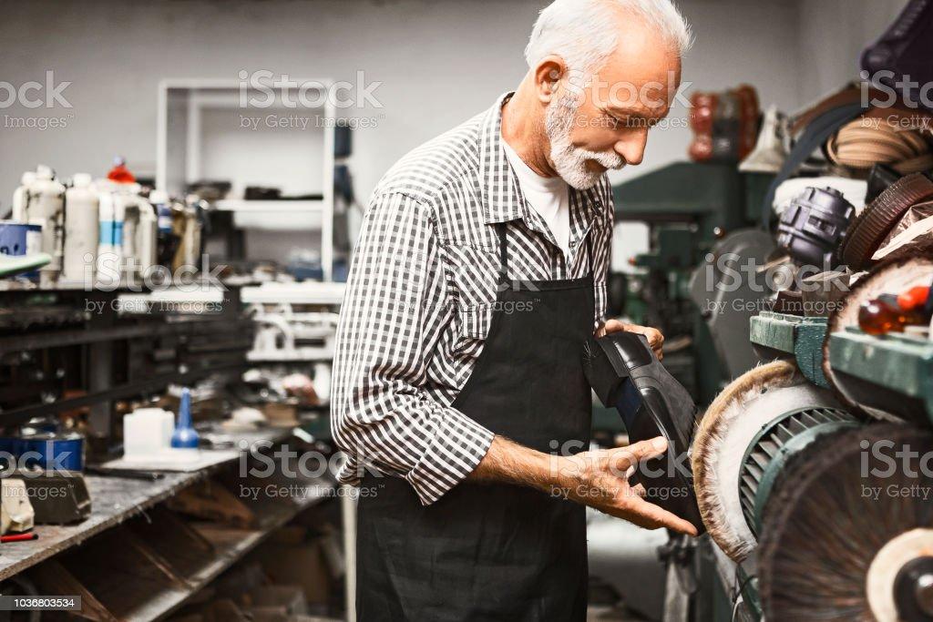 Shoemaker polishing shoes on polishing machine stock photo