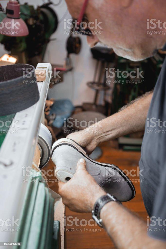 Shoemaker polishing shoes stock photo