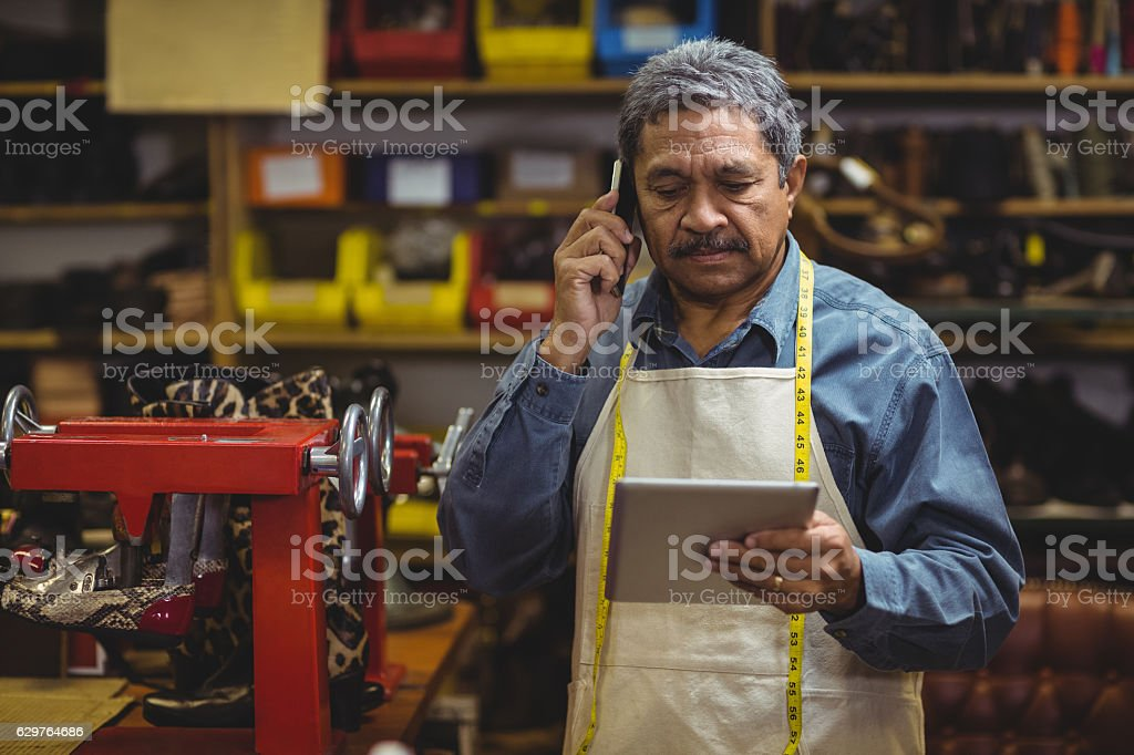 Shoemaker using digital tablet while talking on mobile phone stock photo