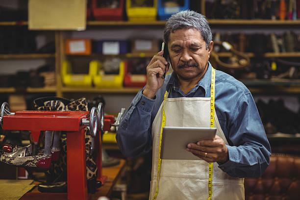 shoemaker using digital tablet while talking on mobile phone - einzelhandelsarbeiter stock-fotos und bilder