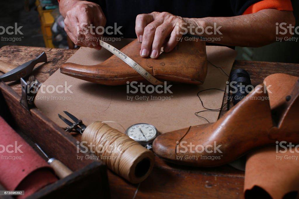 Atelier de cordonnier avec les outils, les chaussures et les lacets - Photo