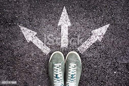 istock Shoes and arrows pointing in different directions on asphalt floor 650197668