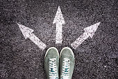 Shoes and arrows pointing in different directions on asphalt floor