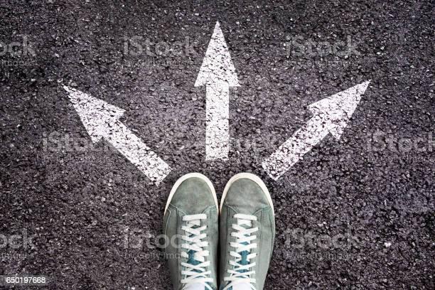 Schuhe Und Pfeile Zeigen In Verschiedene Richtungen Im Asphaltstock Stockfoto und mehr Bilder von Wahlmöglichkeit
