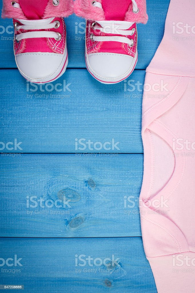 Shoes and bodysuits for newborn, expecting for baby stock photo