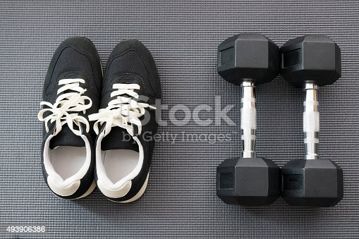 637596492istockphoto Shoes and Dumbbells on Yoga Mat for Workout 493906386