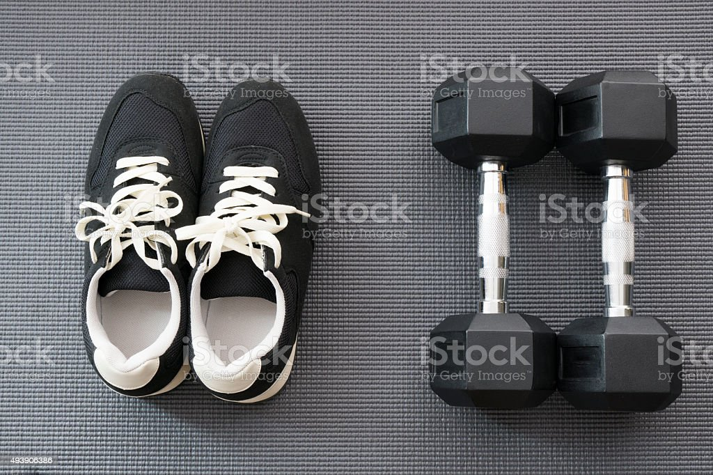 Shoes and Dumbbells on Yoga Mat for Workout stock photo