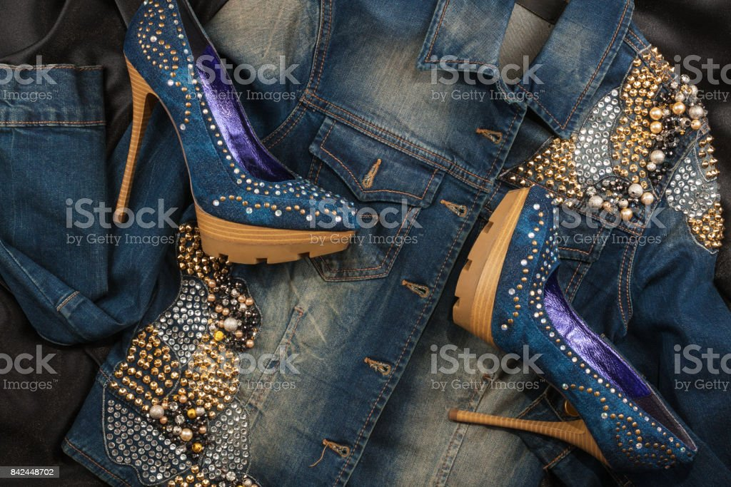 Shoes and jacket from denim fabric inlaid rhinestones lying on a black silk. stock photo