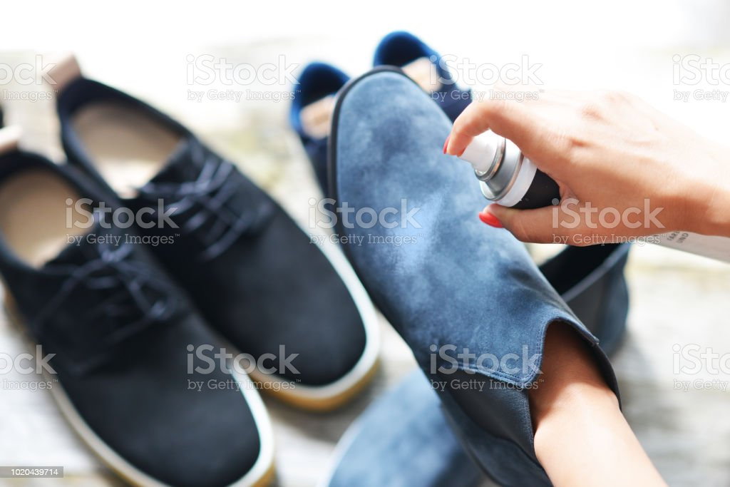 Shoes care concept with woman hands spraying leather shoe stock photo